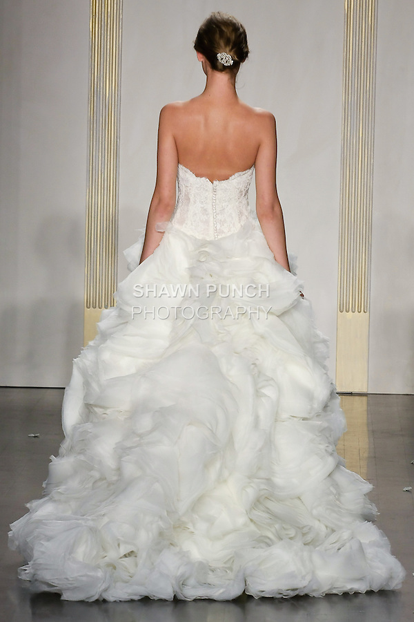 Model walks runway in an ivory organza billowing flounce ball gown, strapless sweetheart neckline, shear alencon lace bodice, dropped waist, layered organza skirt with alencon lace accents, chapel train wedding dress by Lazaro Perez, from the Lazaro Spring 2012 Bridal fashion show.