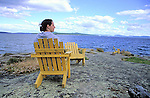 Woman sits in a yellow chair near the water on Vacouver Island, British Columbia, Canada, enjoying the coastal views of the Strait of Georgia.