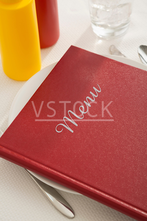 Mustard, ketchup and cutlery on table, menu on plate