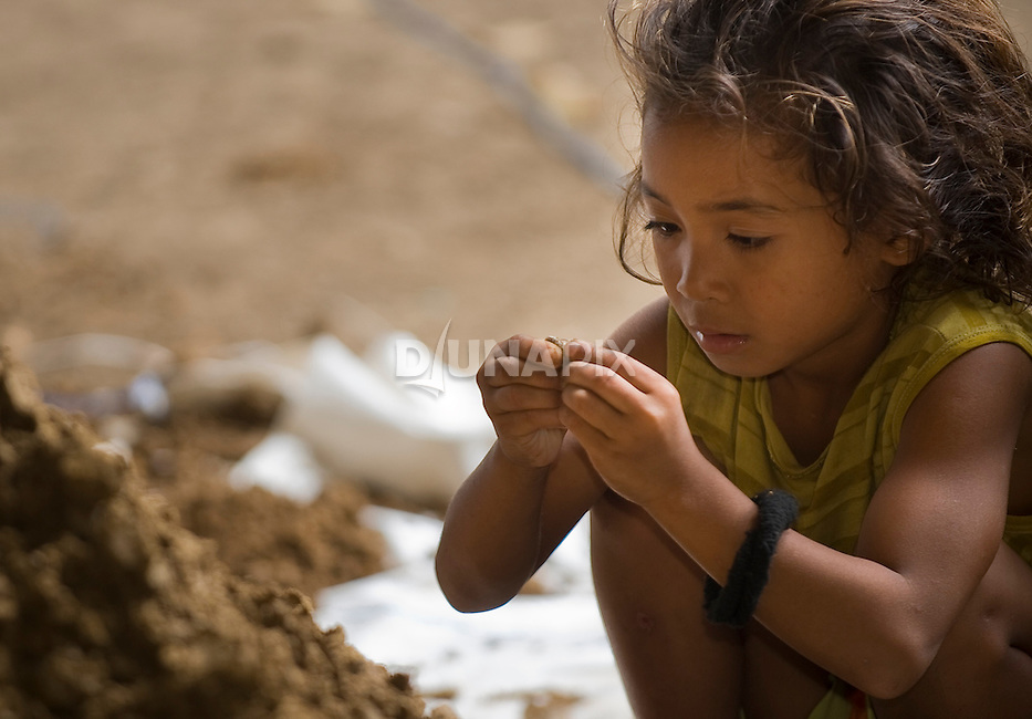 A young Manggarai girl helps her father hunt artefacts in Liang Bua cave.