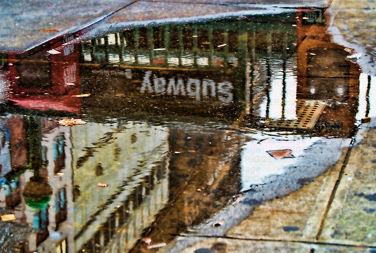 Reflections in a puddle of water showing 34th Street subway station. HDR.