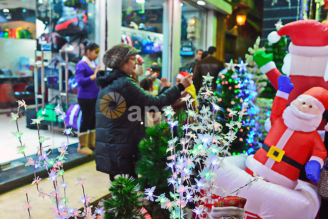 An Egyptian woman takes photos in front of a shop selling Santa Claus dolls as part of Christmas and New Year festivities, in Cairo on December 31, 2014. Photo by Amr Sayed