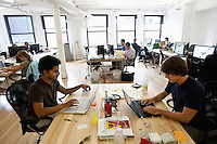 "Dennis Crowley (R) and Naveen Selvadurai, co-founders of social media website Foursquare, work at their desks in their shared office in New York, USA, 5 August 2009. Foursquare, which allows users to stay connected to friends and explore a city, has been dubbed ""the next Twitter"" by an influential tech blog."
