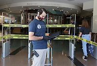 Kyle Vandargriff (cq) monitors visitors Monday, May 18, 2020, at the Fayetteville Public Library.  The library opened with limited hours and social distancing restrictions for the first time since mid-March because of the covid-19 pandemic. Twenty two patrons visited the library within the first 10 minutes of opening. The library will continue to offer online catalog items for curbside pick-up. Library materials can now be returned in drive-by drop boxes. Check out nwaonline.com/200519Daily/ and nwadg.com/photos for a photo gallery.<br /> (NWA Democrat-Gazette/David Gottschalk)