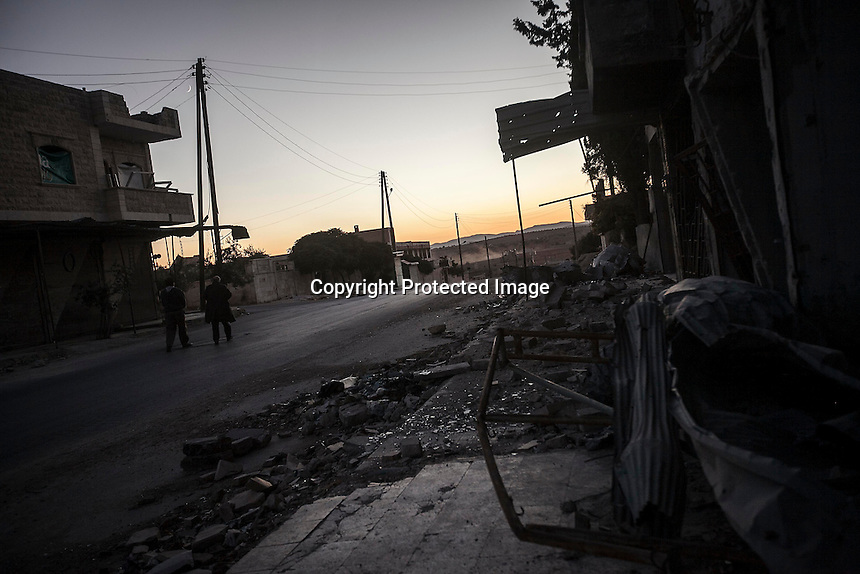 In this Monday, Oct. 07, 2013 photo, Syrian residents walk an empty street damaged by the heavy fighting as smoke rises at the bottom from a mortar shell impact during an attack by opposition fighters (not pictured) over Wadi Al-Deef military post at the frontline in Maraat Anouman in the Idlib province countryside of Syria. (AP/Photo)