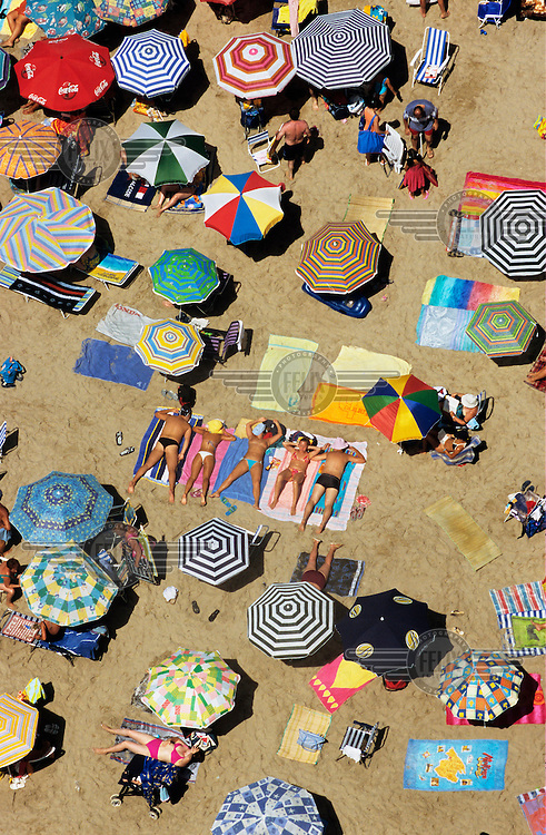 Tourists lying on their towels sunbathe among the parasol umbrellas at the beach.