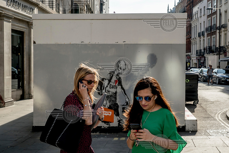 Women using mobile phones on Regent Street beside a piece of street art.