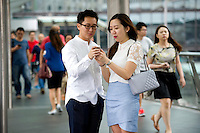 HONG KONG - MAY 05: Beverly Chung and Keith Cheung check a cell phone on a flyover in Central business district, on May 5, in Hong Kong. (Photo by Lucas Schifres/Pictobank)
