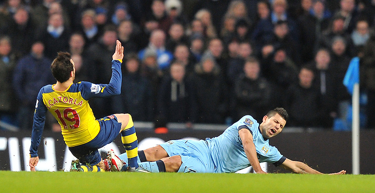 Manchester City's Sergio Ag&uuml;ero is tackled by Arsenal's Santi Cazorla<br /> <br /> Photographer Dave Howarth/CameraSport<br /> <br /> Football - Barclays Premiership - Manchester City v Arsenal - Sunday 18th January 2015 - Etihad stadium - Manchester<br /> <br /> &copy; CameraSport - 43 Linden Ave. Countesthorpe. Leicester. England. LE8 5PG - Tel: +44 (0) 116 277 4147 - admin@camerasport.com - www.camerasport.com