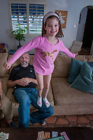 Jack Friedman spends quality time with his grandchildren including Emilia Root (pink shirt) both 7, who decides to practice her balancing skills, in the childrens' Phoenix home.