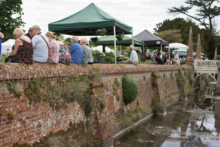 Helmingham Hall gardens in Suffolk England. The Plant Fayre with members of the public sitting on the moat wall