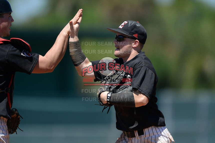 Edgewood Eagles Pat Manning (4) high fives catcher Garrett Bogucki (left) after the second game of a doubleheader against the Plymouth State Panthers on March 17, 2015 at Terry Park in Fort Myers, Florida.  Edgewood defeated Plymouth State 9-2.  (Mike Janes/Four Seam Images)