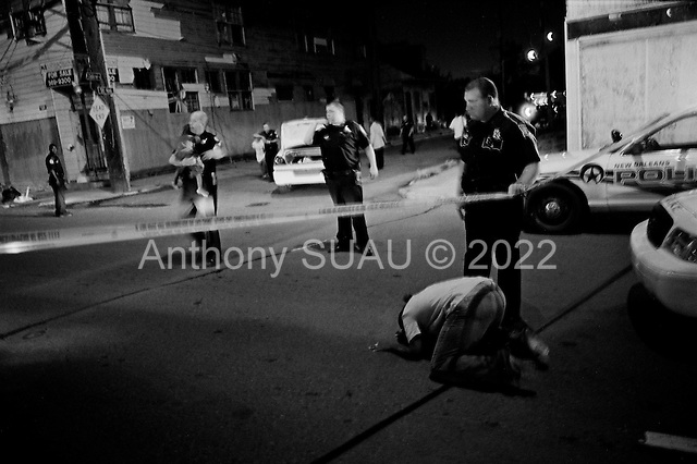 New Orleans, Louisiana.USA.July 28, 2006..A quadruple homicide in the city center on a Friday night. Crime is on the rise as residents return looking for work and living in questionable housing conditions. Younger drug lords try to claim territory in the new destroyed New Orleans nearly one year after hurricane Katrina hit and the levees broke leaving 80% of the city flooded. ...Juanita Thomas, an aunt of three of the slain victims, cries at the scene of the murders as another relatives baby is carried out of the crime scene by a policeman.
