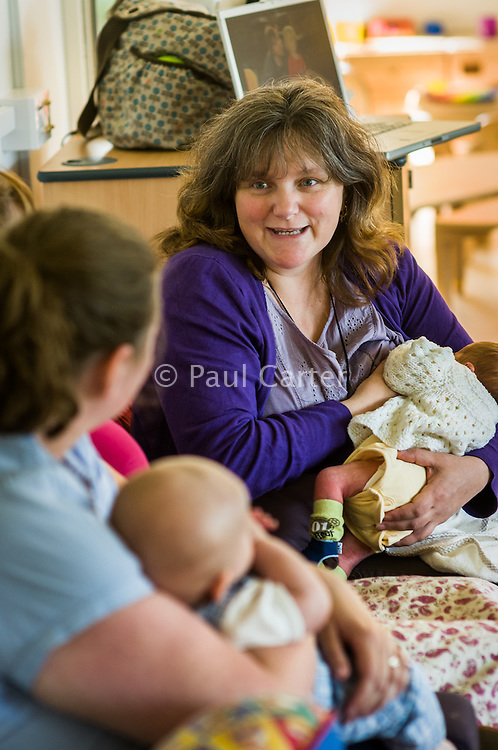 Woman talking to friends while breastfeeding her baby at a drop-in breastfeeding support centre.<br /> <br /> 04 May 2011<br /> Hampshire, England, UK