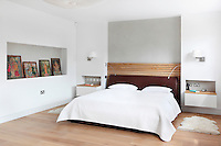 A modern white bedroom with a double bed with a leather headboard. Two wall-mounted bedside tables are set in recesses alongside with a wall light above.