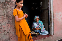 Nafeesa, 27, rolls bidis (indian cigarettes) as her eldest daughter of 4 children aged 10, 7, 4, and 1.5 years, stands nearby in her house compound in a slum in Tonk, Rajasthan, India, on 19th June 2012. Nafeesa's health deteriorated from bad birth spacing and over-working. While her husband works far from home, she rolls bidis to make an income and support the family. She single-handedly runs the household and this has taken a toll on her health and financial insufficiencies has affected her children's health. Photo by Suzanne Lee for Save The Children UK