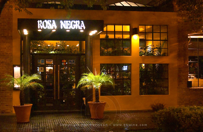The entrance to the restaurant with two palm trees and neon sign. The Rosa Negra Restaurant, The Black Rose, Buenos Aires Argentina, South America
