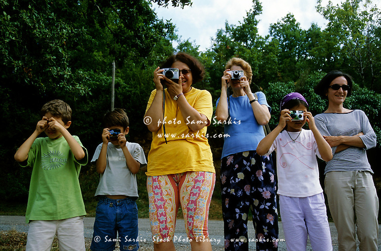 Group of women and children have fun attempting to take a photo all at the same time.