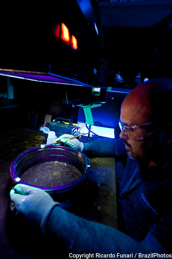 Factory worker, aerospace industry - NDT ( Nondestructive testing ),  Fluorescent penetrant inspection performed by NDT inspector in a darkened environment, to produce a visible indication of surface-breaking discontinuities, Brazil.
