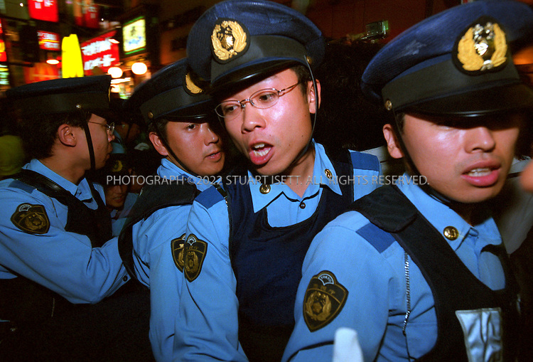 6/7/2002--Tokyo, Japan..Unable to speak English, Japanese police hold up signs in Tokyo's Roppongi entertainment district as they attempt to control England supporters celebrating after their 1-0 victory over Argentina in Sapporo, Japan.....All photographs ©2003 Stuart Isett.All rights reserved.This image may not be reproduced without expressed written permission from Stuart Isett.