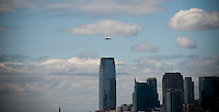 The Enterprise space shuttle, strapped to the back of a 747 jumbo jet,  is flown over the Hudson River for its grand arrival in New York on Friday, April 27, 2012. The shuttle will eventually be put on display at the Intrepid Sea, Air and Space Museum where it is expected to draw more than one million visitors annually and increase tourist revenue for the city by $100 million. The shuttle is directly over the Goldman Sachs building in Jersey City, NJ.(© Richard B. Levine)