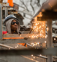 STAFF PHOTO ANTHONY REYES &bull; @NWATONYR<br /> Jahreim Shoats, (CQUED) with ARK Wrecking Co. of Oklahoma, based in Tulsa, uses an acetylene torch Monday, Dec. 22, 2014 to remove seats in Jarrell Williams Bulldog Stadium in Springdale. The home stands and press box are being removed to make way for new structures. Construction should be completed in time for the 2015 football season.