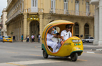Havana, Cuba - A three-wheeled Coco Taxi, so called because it is shaped like a coconut, passes in front of Hotel Plaza near Parque Central.