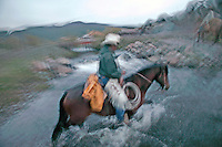 At the end of a cold rainy day, a cowboy crosses a stream heading home.