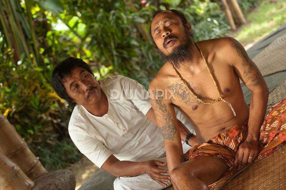 Balinese healers exchange treatments during a break.