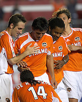 Teammates look on as Houston Dynamo's Dwayne De Rosario polishes Brian Ching's mythical golden boot after Ching scored his fourth goal in a single game.  The Houston Dynamo beat the Colorado Rapids 5-2 on April 2, 2006 at Robertson Stadium in Houston, TX.