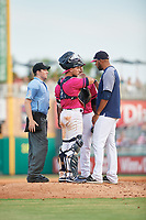 Pensacola Blue Wahoos pitching coach Cibney Bello (right) talks with pitcher Edwar Colina (26) and catcher Ben Rortvedt (1) as umpire Tyler Jones listens in during a Southern League game against the Mobile BayBears on July 25, 2019 at Blue Wahoos Stadium in Pensacola, Florida.  Pensacola defeated Mobile 2-1 in the first game of a doubleheader.  (Mike Janes/Four Seam Images)