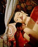 SRI LANKA; Asia; young monk standing by Buddha statue