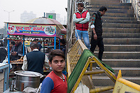 Food vendors and pedestrians are seen by an overpass at HUDA City Centre in Gurugram, Haryana, India, on Mon., December 10, 2018.