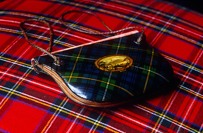 An antique tartan purse is displayed on a bright red tartan blanket