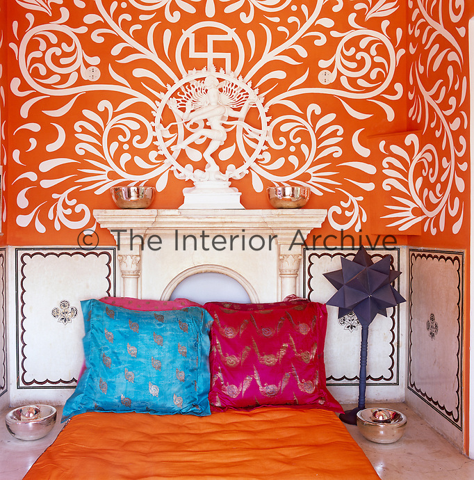 A small room with vibrant orange and white hand-painted stencilled walls houses a mattress covered in silk
