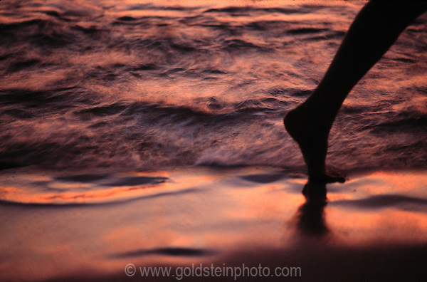 Woman's leg making footsteps in the sand at sunset. Puerto Vallarta, Mexico