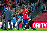 Alvaro Morata of Spain appears to help a pitch invaded who was looking for a selfie as stewards tackle him during the International Friendly match between England and Spain at Wembley Stadium, London, England on 15 November 2016. Photo by Andy Rowland.