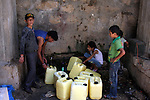 A Palestinian boys fill bottles of water in the West Bank village of Qarawah Bani Zeid on August 8, 2009. According to the World Bank, the Palestinians have limited access to potable water, especially in the West Bank, where estimated consumption levels are well below international standards. Photo by Issam Rimawi