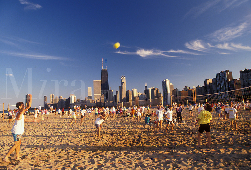 AJ2787, Chicago, volleyball, skyline, Illinois, People playing volleyball games on the beach along Lake Michigan at North Avenue Park with skyline of downtown Chicago in the background in the state of Illinois.