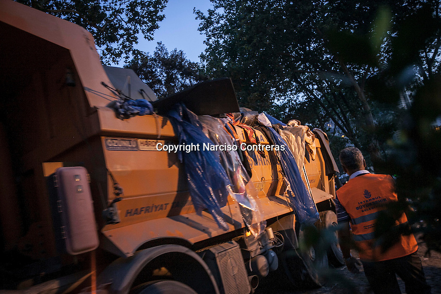 In this Sunday, Jun. 16, 2013 photo, workers clean Gezi park from the tents after anti-riot police attacked and evicted the night before the protesters during the ongoing turmoil in Istanbul, Turkey. (Photo/Narciso Contreras).