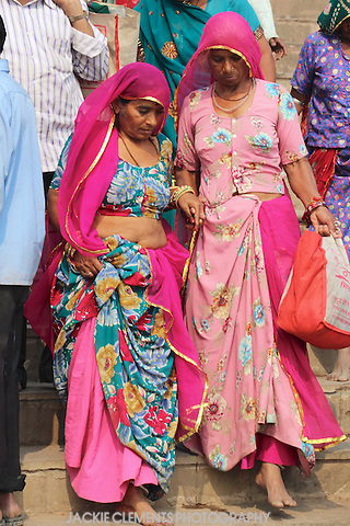 Two women in bright traditional dress help each other down the steep ghat steps to the Ganges River