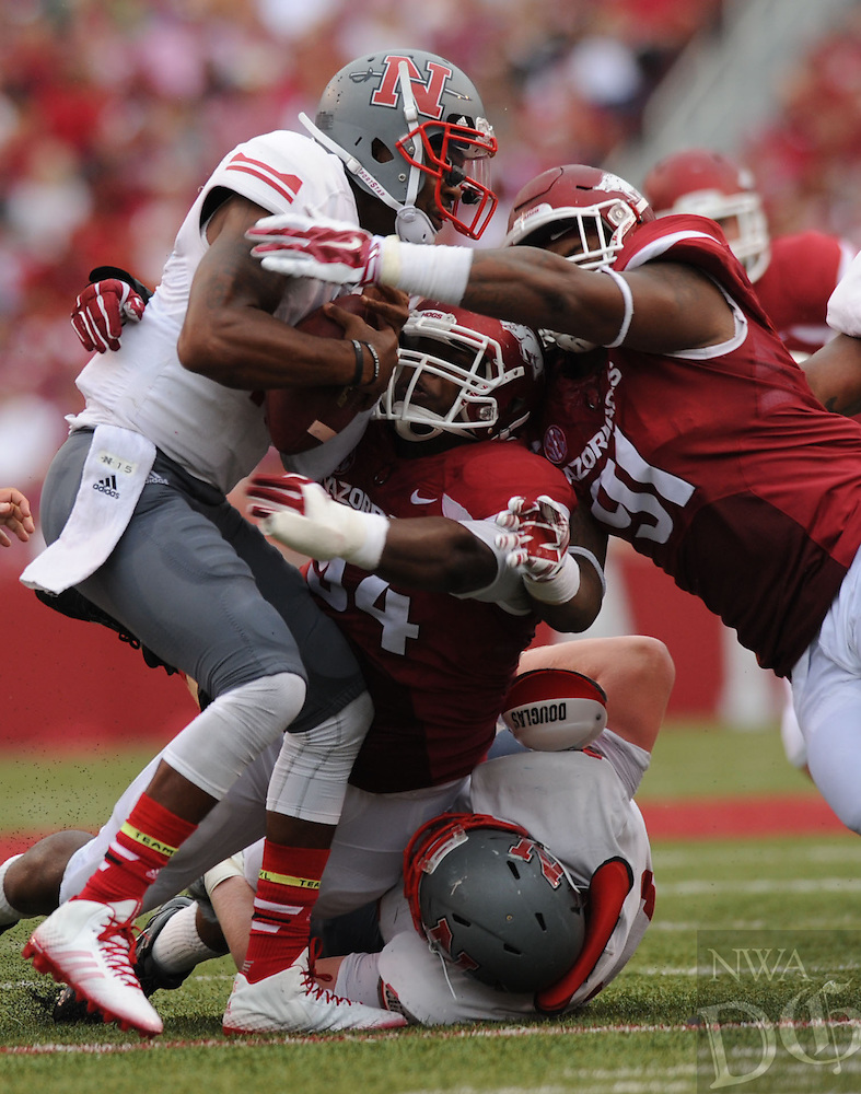 NWA Media/ANDY SHUPE - Nicholls quarterback Kalen Henderson, left, is sacked by Arkansas defensive tackles Darius Philon (91) and Taiwan Johnson (94) during the second quarter Saturday, Sept. 6, 2014, at Razorback Stadium in Fayetteville