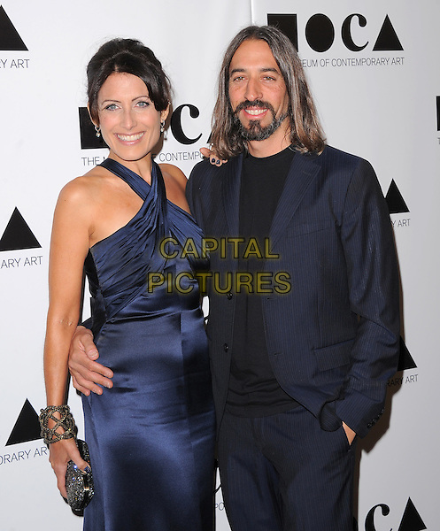 "Lisa Edelstein & Guest .at The 2011 MOCA Gala ""An Artist's Life Manifesto"" With Artistic Direction From Marina Abramovic held at MOCA Grand Avenue in Los Angeles, California, USA, .November 12th 2011..half length  smiling  navy blue  silk satin halterneck  clutch bag silver                                   .CAP/RKE/DVS.©DVS/RockinExposures/Capital Pictures."