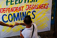 """José Corredor (""""Runner"""") paints letters on a promotional banner in the sign painting workshop in Cartagena, Colombia, 14 April 2018. Hidden in the dark, narrow alleys of Bazurto market, a group of dozen young men gathered around José Corredor (""""Runner""""), the master painter, produce every day hundreds of hand-painted posters. Although the vast majority of the production is designed for a cheap visual promotion of popular Champeta music parties, held every weekend around the city, Runner and his apprentices also create other graphic design artworks, based on brush lettering technique. Using simple brushes and bright paints, the artisanal workshop keeps the traditional sign painting art alive."""