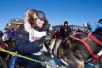 Matt Hayashida congratulates his dogs at Nome finish line during the 2010 Iditarod