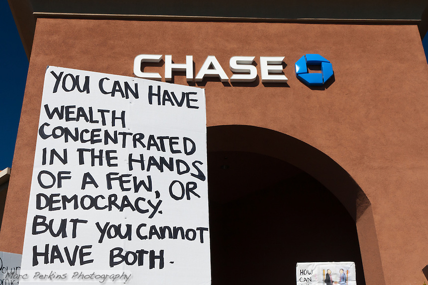 "A sign reading ""You can have wealth concentrated in the hands of a few, or democracy.  But you cannot have both"" is held in front of a Chase bank building during the Occupy Orange County, Irvine march on Saturday November 5."
