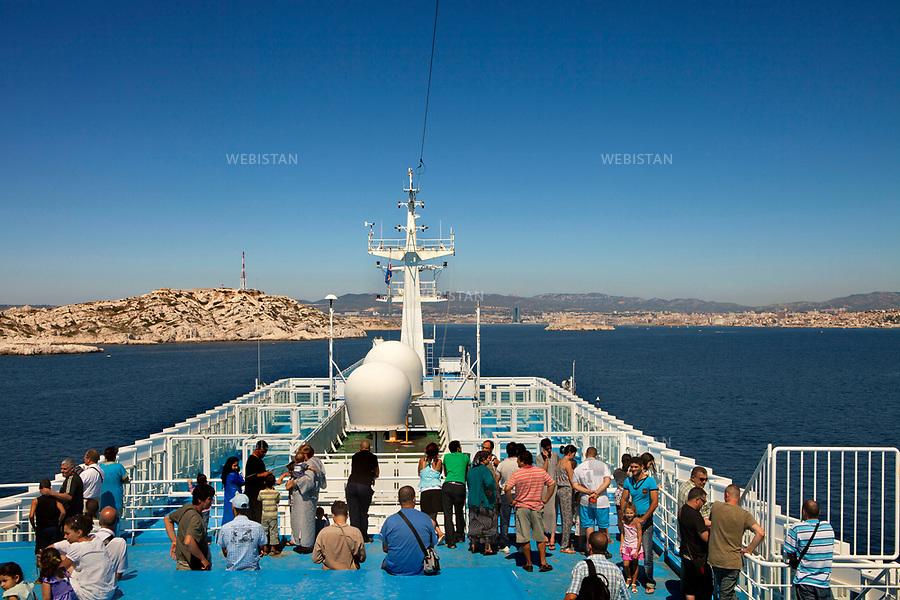 Mer medit&eacute;rran&eacute;e. 11 aout 2011. Des passagers sur le pont du bateau qui relie Marseille &agrave; Alger, &agrave; l'approche de la c&ocirc;te alg&eacute;rienne.<br /> <br /> Mediterranean Sea. August 11th 2011. Passengers on deck of the boat that connects Marseille to Algiers, at the approach of the Algerian coast.