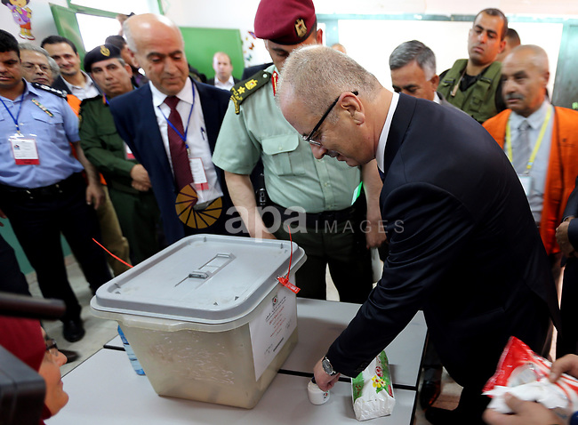 Palestinian Prime Minister Rami Hamdallah has his finger stained with ink as he casts his ballot at a polling station during municipal elections in the northern West Bank town of Anabta, near Tulkarm May 13, 2017. Photo by Prime Minister Office