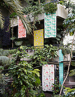 Interior of Barbican conservatory. Photographed towards two stone balconies with hanging fabrics. The top balcony has two fabrics hanging down on the left side. The left hand one is a red print and right side is a green, floral print. On the lower balcony, stands another sheet of fabric, yellow and floral in design. Two further sheets of fabric hang from this balcony. One is a white and red, floral design and the other, a turquoise, geometric print. The whole image is very green and plant dominated.