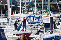CARDIFF, UK. 2nd April 2017. Two men work on a boat in Penarth Marina in sunny weather.